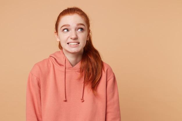 Śliczna, młoda rudowłosa kobieta z niebezpiecznie związanymi włosami w kucyk