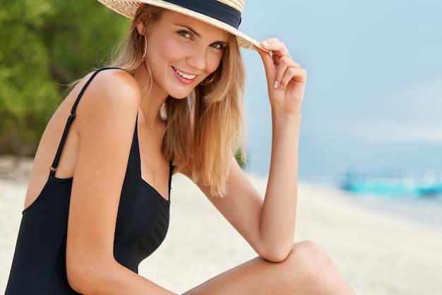 Śliczna młoda śliczna kobieta pozuje samotnie na tropikalnej plaży, ma opaloną skórę, nosi kostium kąpielowy i letni kapelusz, lubi relaks. styl życia na wyspie. zadowolona podróżniczka odpoczywa na spokojnym oceanie