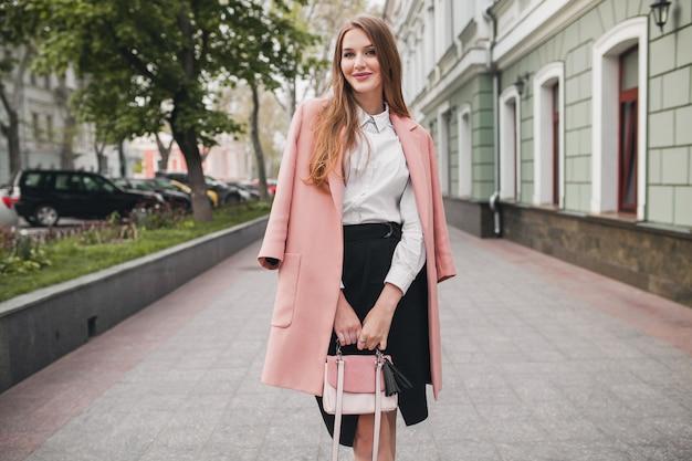 Śliczna młoda stylowa piękna kobieta spacerująca ulicą, ubrana w różowy płaszcz, torebkę, białą koszulę, czarną spódnicę, strój modowy, trend jesienny, uśmiechnięty szczęśliwy, akcesoria