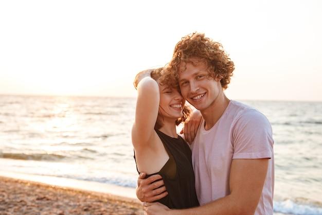 Śliczna młoda szczęśliwa kochająca para przytulanie na zewnątrz na plaży