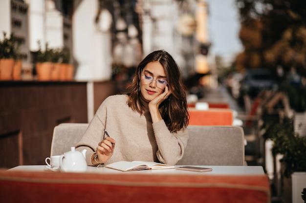 Śliczna młoda uczennica z brunetką falującą fryzurą w beżowym swetrze i okularach skoncentrowała się na nauce na tarasie kawiarni miejskiej w słoneczny jesienny dzień