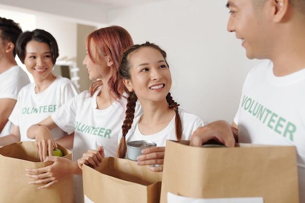 Śliczna młoda uśmiechnięta kobieta jako wolontariuszka z przyjaciółmi w centrum darowizn i pakująca artykuły spożywcze dla uchodźców lub osób w potrzebie