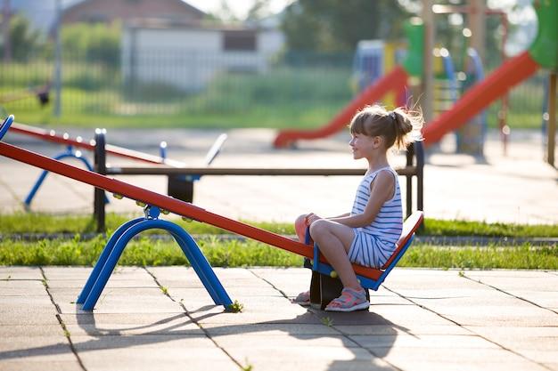 Śliczna młode dziecko dziewczyna outdoors na saw huśtawce na pogodnym letnim dniu