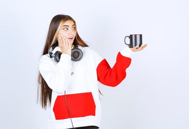 Śliczna modelka stojąca w słuchawkach i trzymająca filiżankę napoju