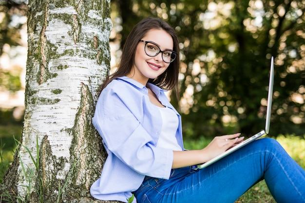 Śliczna modelka w niebieskich dżinsach współpracuje z laptopem w parku miejskim