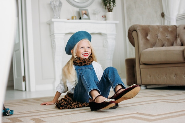 Śliczna modna modna jasnowłosa dziewczynka ubrana w drelichowy kombinezon, szal lamparta i niebieski beret z akcesoriami mamy. córka imituje mamę