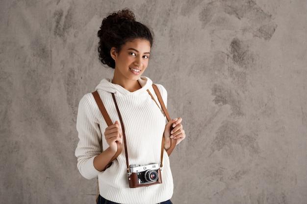 Śliczna modniś kobieta bierze fotografie na retro kamerze