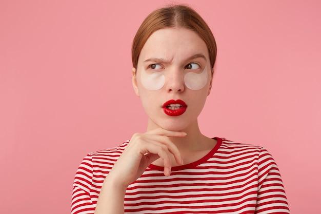Śliczna, myśląca młoda rudowłosa dziewczyna z czerwonymi ustami i łatami pod oczami, ubrana w czerwoną koszulkę w paski, dotyka policzka, odwraca wzrok, wstaje.
