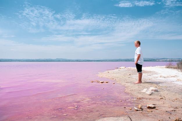 Śliczna nastolatek chłopiec jest ubranym lato odzieżową pozycję na różowym jeziorze