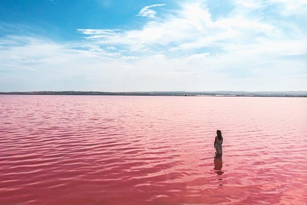 Śliczna nastolatek dziewczyna jest ubranym biel suknię w wodzie zadziwiający różowy jezioro