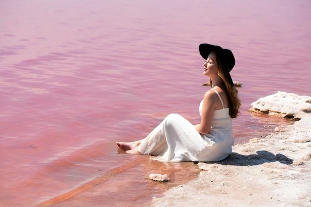 Śliczna nastolatek kobieta jest ubranym biel sukni obsiadanie na zadziwiającym różowym jeziorze