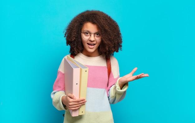 Śliczna nastolatka afro czuje się szczęśliwa, zaskoczona i pogodna, uśmiechnięta z pozytywnym nastawieniem, realizująca rozwiązanie lub pomysł. koncepcja studenta