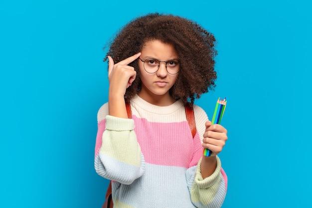 Śliczna nastolatka afro czuje się zdezorientowana i zdezorientowana, pokazując, że jesteś szalony, szalony lub oszalały. koncepcja studenta