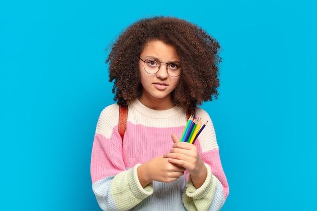 Śliczna nastolatka afro czuje się zdezorientowana i zdezorientowana, z tępym, oszołomionym wyrazem twarzy, patrzącym na coś nieoczekiwanego. koncepcja studenta