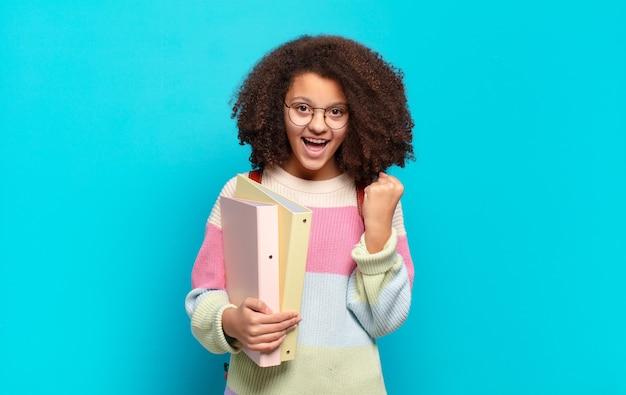 Śliczna nastolatka afro czuje się zszokowana, podekscytowana i szczęśliwa, śmiejąc się i świętując sukces, mówiąc wow!. koncepcja studenta