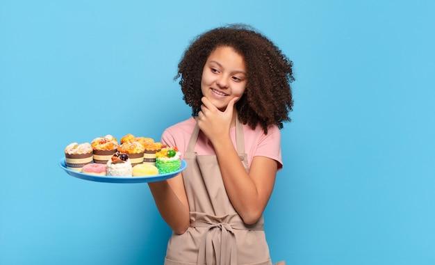 Śliczna nastolatka afro uśmiechnięta ze szczęśliwym, pewnym siebie wyrazem twarzy z ręką na brodzie, zadumana i patrząca w bok. humorystyczna koncepcja piekarza