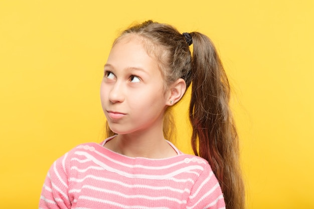 Śliczna nastolatka patrząc w górę i na boki. portret na żółto.