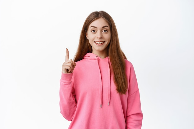 Śliczna nastolatka pokazująca tekst promocyjny, wskazujący palec w górę i uśmiechający się z przodu, poleca firmę, pokazuje reklamę, biała ściana