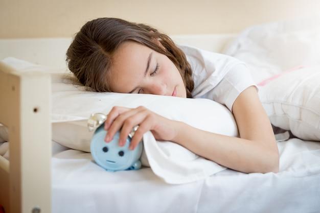 Śliczna nastolatka trzymająca budzik pod poduszką