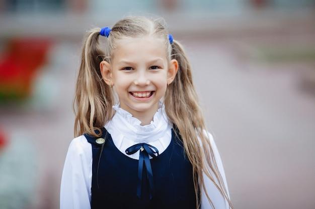 Śliczna nastolatka uczennica w mundurze z kucykami, uśmiechnięta, pozuje do kamery.