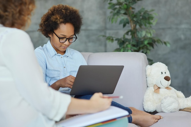 Śliczna nastolatka w okularach słucha swojej nauczycielki, która używa laptopa do nauki podczas