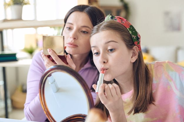 Śliczna nastolatka z długimi blond włosami, nakładająca różową szminkę i patrząca w lustro z matką z otwartym pudrem kompaktowym