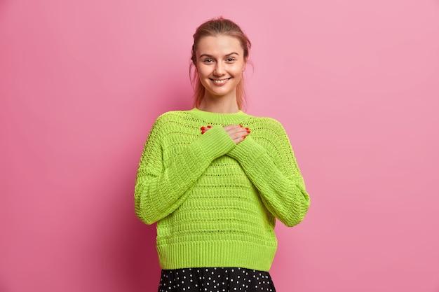 Śliczna nastolatka z zaczesanymi włosami uśmiecha się przyjemnie, wyrażając wdzięczność, robi gest wdzięczności