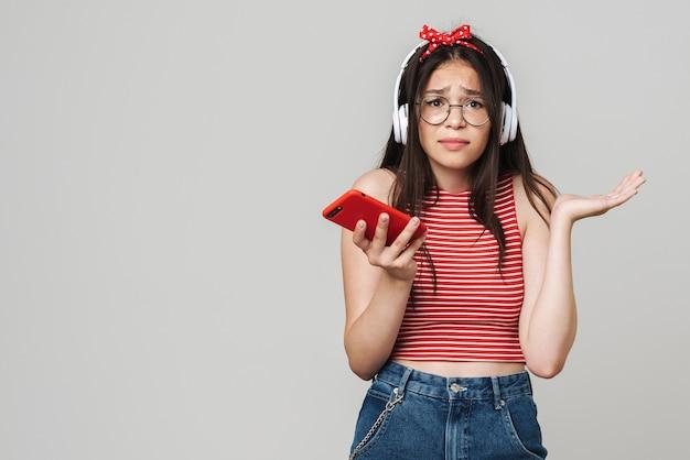 Śliczna nastolatka zdenerwowana zdezorientowana dziewczyna w swobodnym stroju stojąca na białym tle nad szarą ścianą, słuchająca muzyki przez słuchawki, używająca telefonu komórkowego