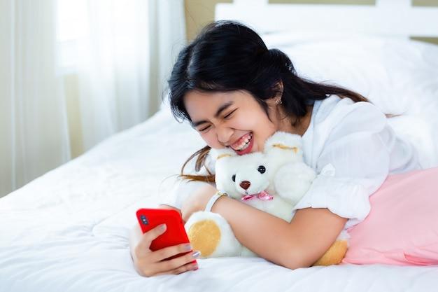 Śliczna nastoletnia kobieta radosna z smartphone na łóżku