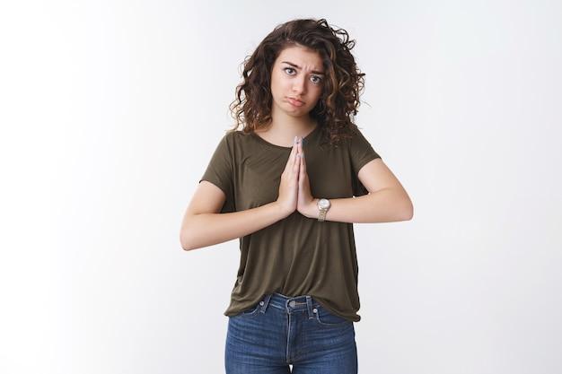 Śliczna, nędznie wyglądająca młoda kobieta z kręconymi włosami rasy kaukaskiej dąsa się robiąc żałosny smutny grymas ściśnij dłonie razem modlą się błagając o pomoc z nadzieją patrząc jęcząc chcę przysługę powiedz proszę
