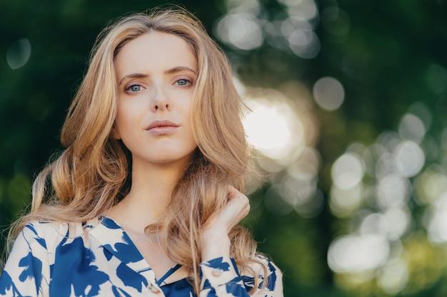 Śliczna niebieskooka wspaniała kobieta o długich falowanych włosach ma przemyślany wyraz twarzy