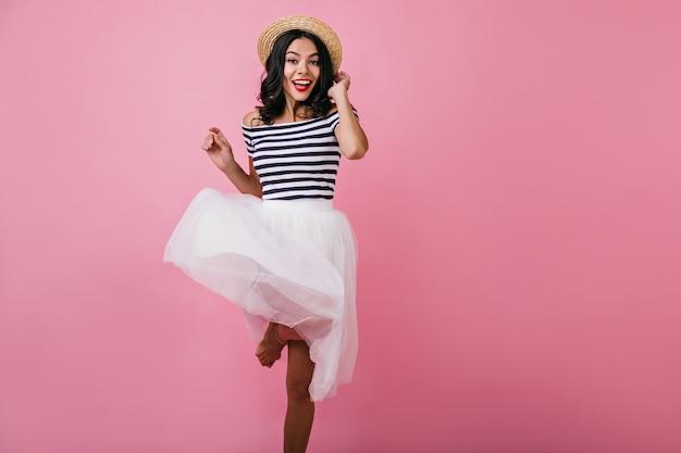 Śliczna opalona kobieta w modnych pasiastych podkoszulkach skacze z uśmiechem. kryty zdjęcie atrakcyjnej dziewczyny brunetka, śmiejąc się i tańcząc.
