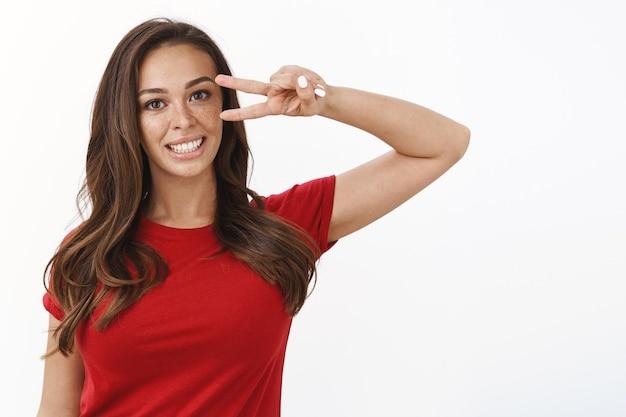 Śliczna, optymistyczna, ambitna młoda dziewczyna z piegami w czerwonej koszulce, wysyłająca entuzjastyczne wibracje, okazująca pokój lub zwycięstwo znak dobrej woli przy oku, uśmiechnięta radośnie, pozująca do zdjęcia na białej ścianie