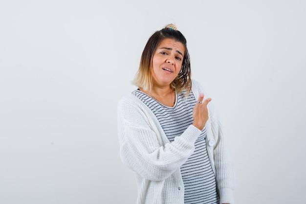 Śliczna pani w t-shirt, sweter skierowany do tyłu i patrząc zdezorientowany, widok z przodu.