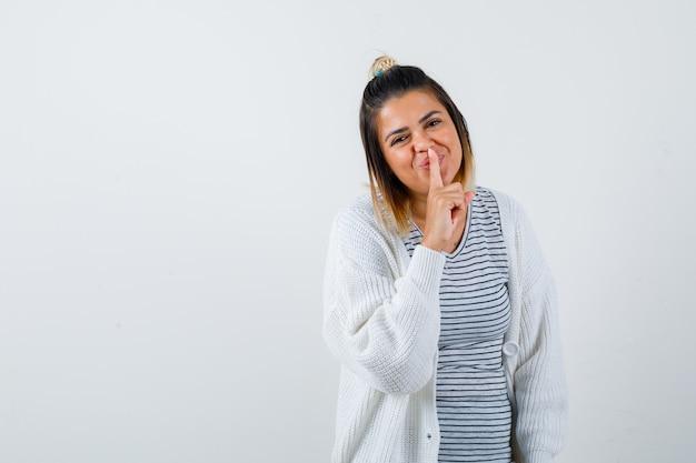 Śliczna pani w t-shirt, sweterek pokazujący gest ciszy i patrzący grzecznie, widok z przodu.