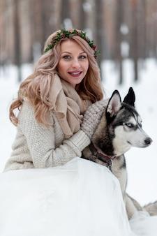 Śliczna panna młoda z wiankiem bawić się z siberian husky na tle białego śniegu. zimowe wesele.
