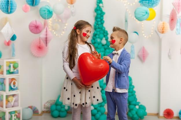 Śliczna para dzieci z balonem czerwone serce. koncepcja walentynki i miłość, łapka