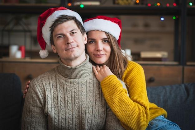 Śliczna para jest ubranym santa kapelusze i pulowery