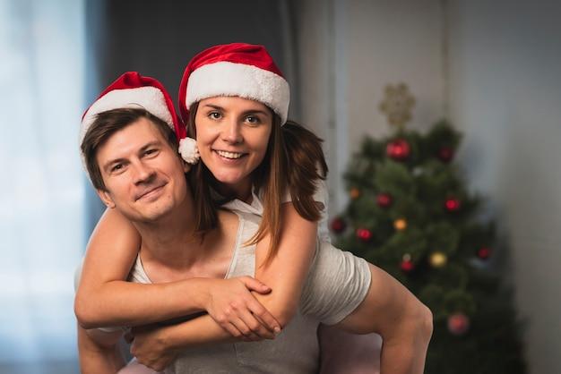 Śliczna para jest ubranym santa kapelusze