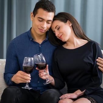 Śliczna para ma szkło wino podczas gdy siedzący na leżance
