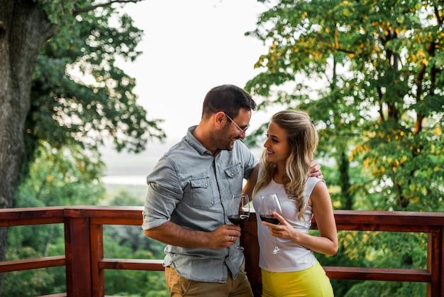 Śliczna para na wakacje. stojąc na balkonie z widokiem na piękną przyrodę.