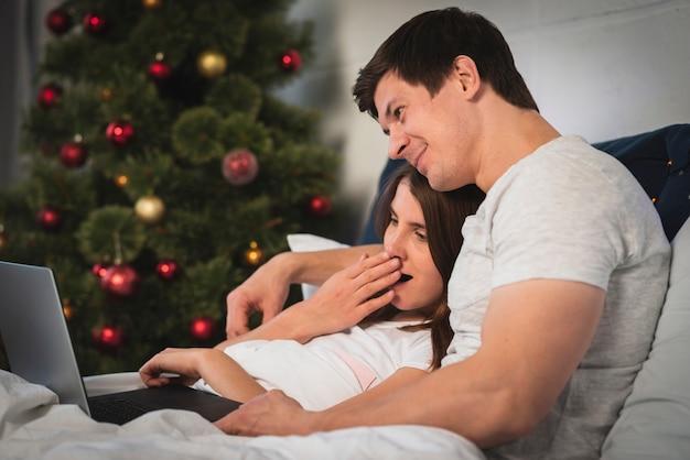Śliczna para patrzeje laptop w łóżku