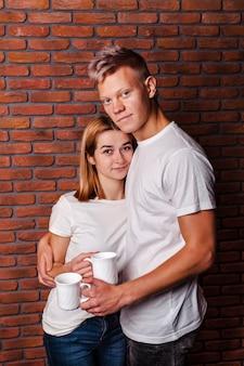 Śliczna para pozuje z ich kawowymi kubkami