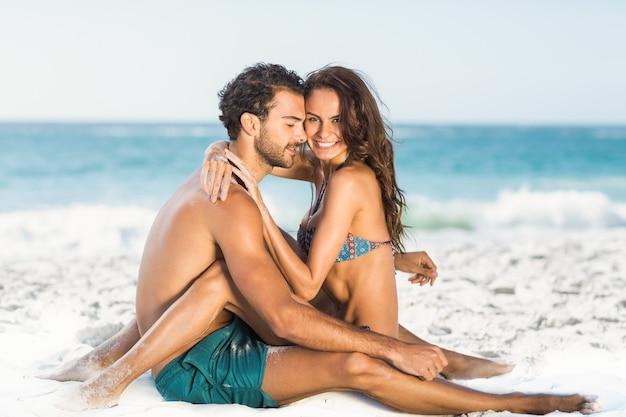 Śliczna para przytulanie siedzi na plaży