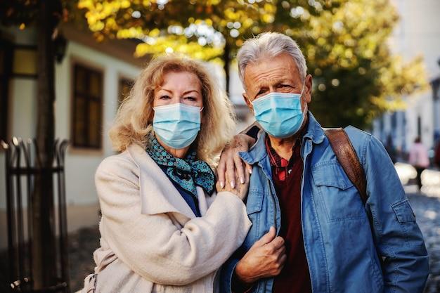 Śliczna para seniorów z maskami ochronnymi na stojąco w starej części miasta.