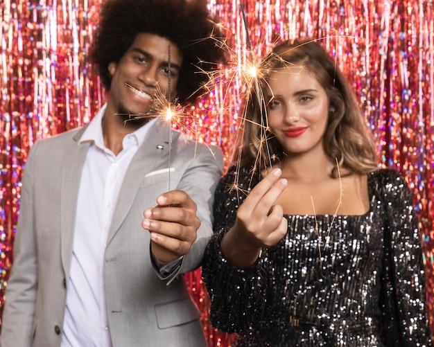 Śliczna para trzyma płonącego sparkler wybuchy