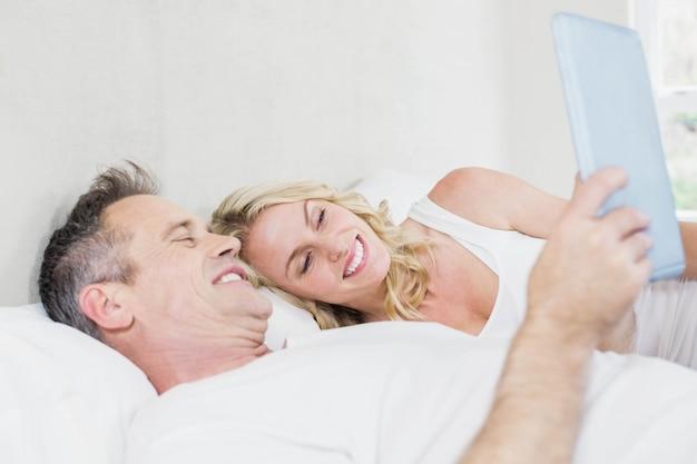 Śliczna para używa pastylkę w łóżku