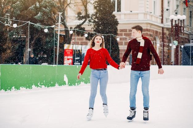 Śliczna para w czerwonych pulowerach ma zabawę w lodowej arenie