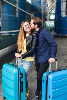 Śliczna para z walizkami stoi na lotnisku na zewnątrz. ma długie włosy, okulary, żółty sweter, kurtkę. nosi czarną koszulę, brodę. facet przytula i całuje dziewczynę.