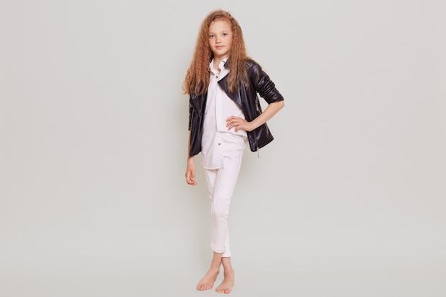 Śliczna pewna siebie uczennica w białej bluzce, spodniach i skórzanej kurtce stoi z ręką na biodrze, patrząc z przodu